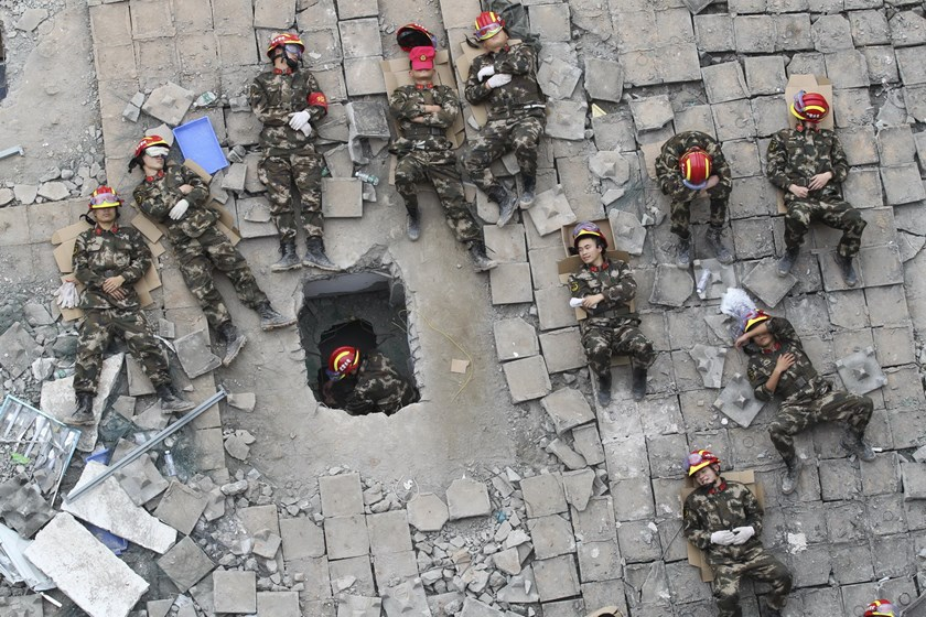 Rescuers sleep among the debris of collapsed buildings during a break of rescue operations after a landslide hit an industrial park on Sunday, in Shenzhen, Guangdong province, China, December 23, 2015. Picture taken December 23, 2015. Photo: Reuters/Stringer