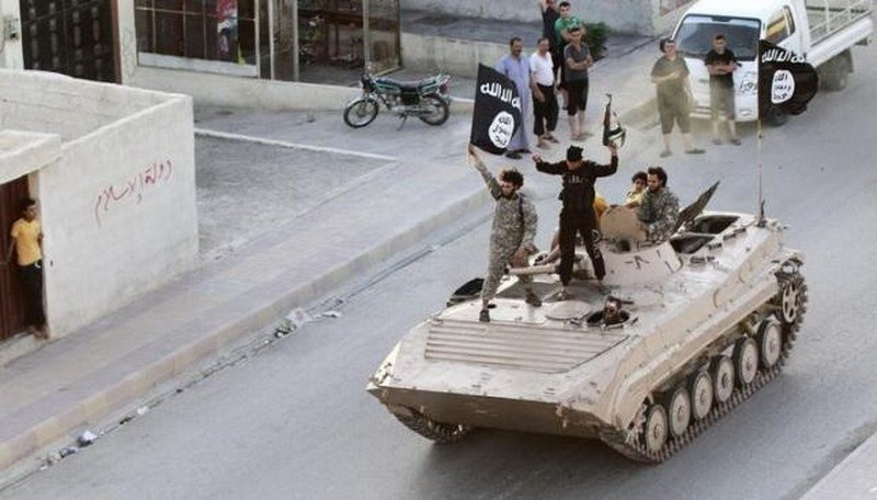 Militant Islamist fighters hold the flag of Islamic State (IS) while taking part in a military parade along the streets of northern Raqqa province in this June 30, 2014 file photo. Photo: Reuters/Stringer/Files