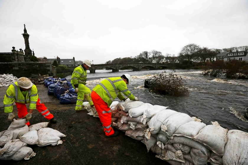Council workers rebuild a wall with sandbags following flooding at Newton Stewart in Scotland, Britain December 31, 2015. Photo: Reuters/Darren Staples