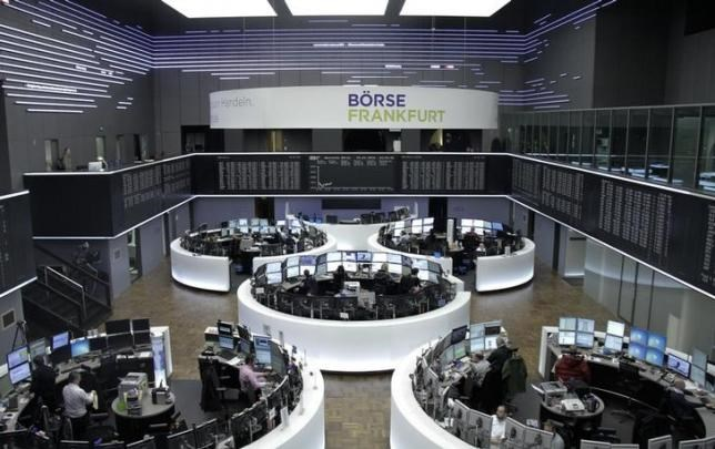 Traders are pictured at their desks in front of the DAX board at the stock exchange in Frankfurt, Germany January 4, 2016. Photo: Reuters/Staff/Remote