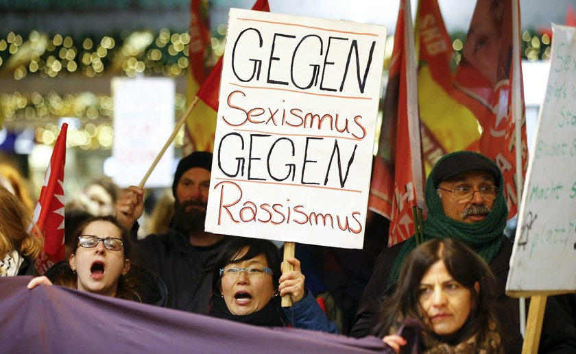"Women shout slogans and hold up a placard that reads ""Against Sexism - Against Racism"" as they march through the main railway station of Cologne, Germany, January 5, 2016. Photo: Reuters/Wolfgang Rattay"