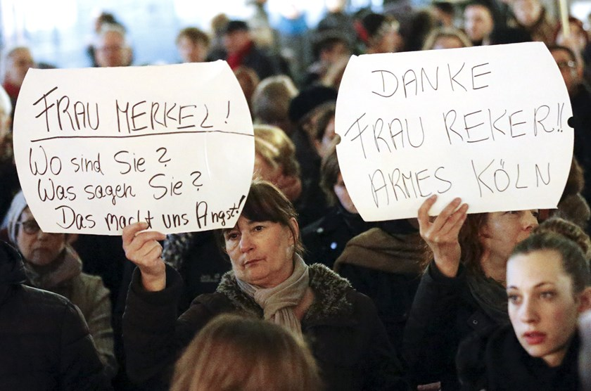 "Women hold up placards that read ""Mrs. Merkel: Where are you? What are you saying? This worries us!"" and ""Thanks (Cologne mayor Henriette) Reker!! Poor Cologne"" (R) during a protest in front of the Cologne Cathedral, Germany, January 5, 2016. Photo: Reuters/Wolfgang Rattay"