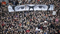People hold panels to create an image depicting the eyes of late Charlie Hebdo editor Stephane Charbonnier, known as 'Charb', as hundreds of thousands of French citizens take part in a solidarity march (Marche Republicaine) in the streets of Paris, in this January 11, 2015 file photo. Photo: Reuters/Charles Platiau/Files