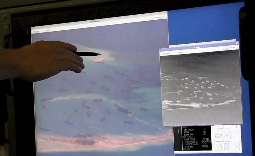A U.S. Navy crewman aboard a P-8A Poseidon surveillance aircraft points to a computer screen purportedly showing Chinese construction on the reclaimed land of Fiery Cross Reef in the disputed Spratly Islands in the South China Sea in this still image from video provided by the United States Navy on May 21, 2015. Photo: Reuters/U.S. Navy/Handout via Reuters/Files