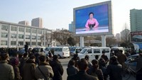 People watch a huge screen broadcasting the government's announcement in Pyongyang, North Korea, in this photo released by Kyodo January 6, 2016. REUTERS/Kyodo