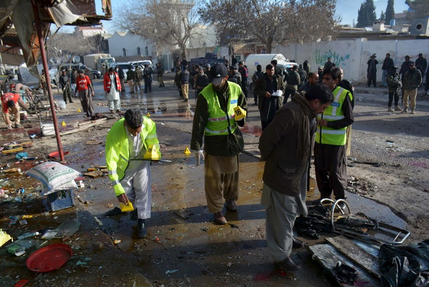 Crime scene investigators collect evidence from the site of a suicide bomb attack close to a polio eradication center in Quetta, Pakistan, January 13, 2016. Photo: Reuters/Stringer