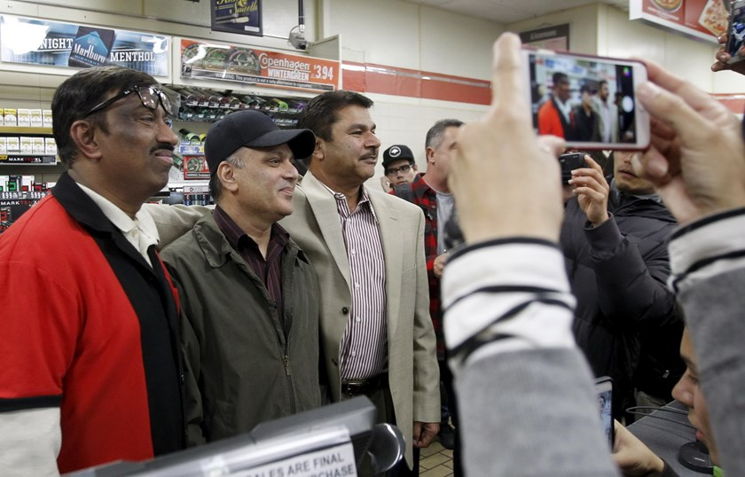 7-Eleven store clerk M. Faroqui (L), manager Bally Gosal (C), and owner Balbir Atwal pose for photographs for customers as they celebrate after selling a winning Powerball ticket, in Chino Hills, California January 13, 2016. A winning ticket was sold there for the massive $1.59 billion Powerball lottery on Wednesday, officials said after drawing the winning numbers for the world's largest potential jackpot for a single player. Photo: Reuters/Alex Gallardo