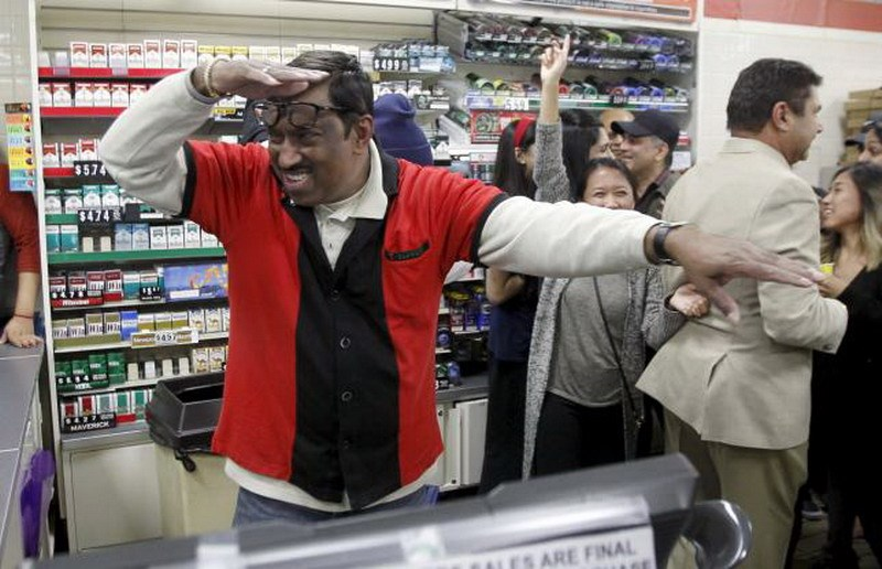 7-Eleven store clerk M. Faroqui celebrates after selling a winning Powerball ticket, in Chino Hills, California January 13, 2016. Photo: Reuters/Alex Gallardo