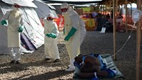 This file photo taken on November 15, 2014 shows health workers wearing protective equipment dance as they try to cheer up an Ebola patient at Kenama treatment center run by the Red Cross Society on November 15, 2014. Photo: AFP/Francisco Leong