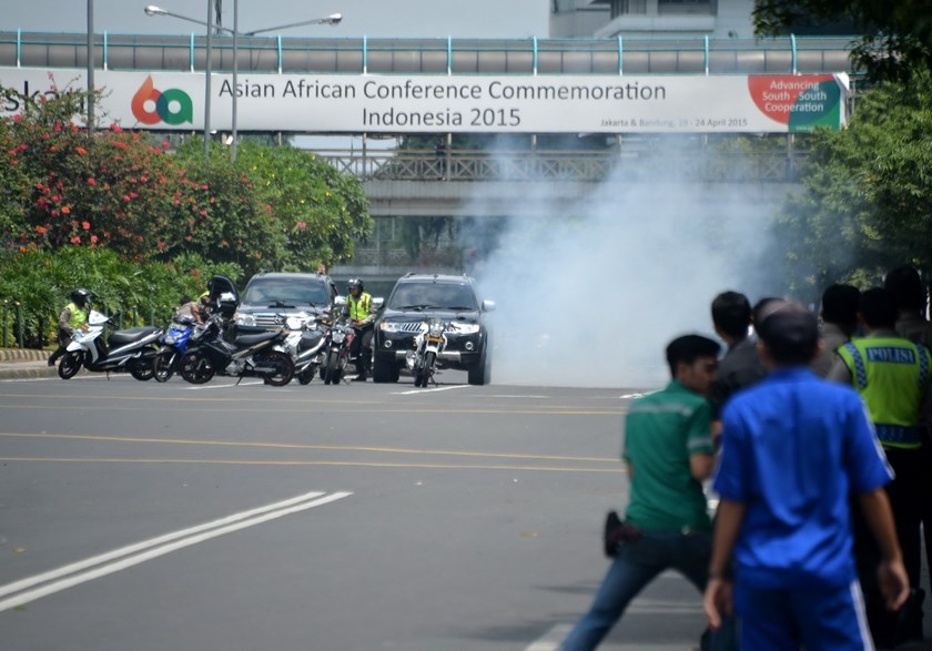 Police (L) hide behind vehicles during an exchange of gunfire with suspects hiding near a Starbucks cafe when another blast happens in Jakarta on January 14, 2016. Photo: AFP/ Bay ISMOYO