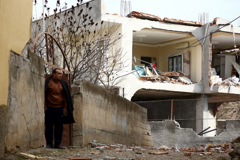 A man stands next to a building, damaged after a truck bomb attack on a nearby police station, in Cinar in the southeastern city of Diyarbakir, Turkey, January 14, 2016. Photo: Reuters/Sertac Kayar