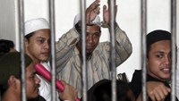 Radical Muslim cleric Aman Abdurrahman (C), also known as Oman Rochman, raises his hands in a holding cell as he waits with other militants for their trial in Jakarta, in this August 26, 2010 file photo. Photo: Reuters/Dadang Tri/Files