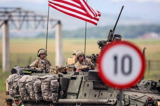 U.S. troops sit on the top of a military vehicle as their convoy passes near Malu village, Romania May 13, 2015. Reuters/Ovidiu Micsik/Inqua Photos