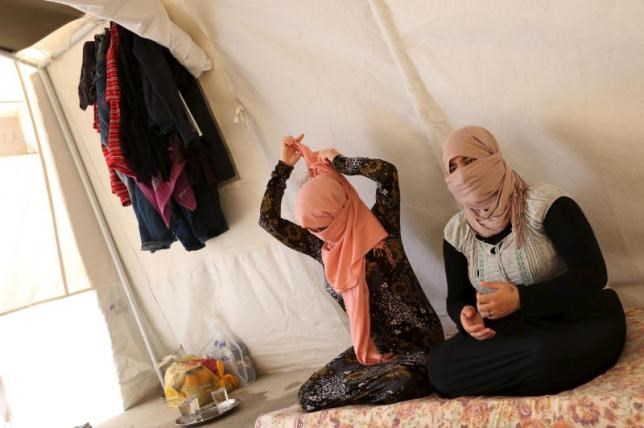 Yazidi sisters, who escaped from captivity by Islamic State (IS) militants, sit in a tent at Sharya refugee camp on the outskirts of Duhok province July 3, 2015. Photo: Reuters/Ari Jala