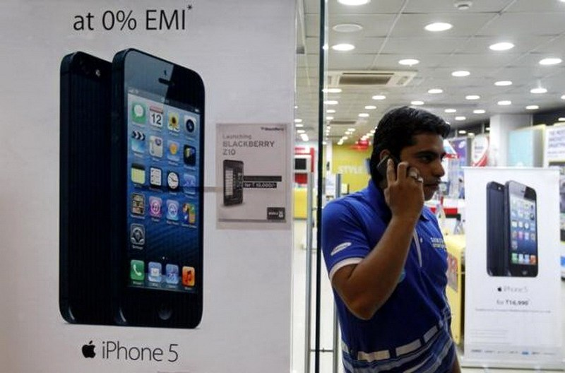 A man speaks on his mobile phone while standing next to posters advertising an Apple iPhone 5 and Blackberry Z10 in Ahmedabad February 22, 2013. Photo: Reuters/Amit Dave/Files