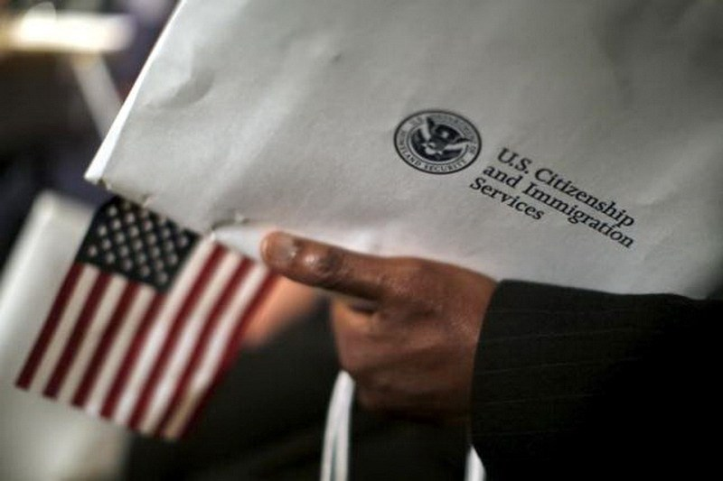 A man holds an envelope from the U.S. Citizenship and Immigrations Service during a naturalization ceremony at the National Archives Museum in Washington December 15, 2015. Photo: Reuters/Carlos Barria
