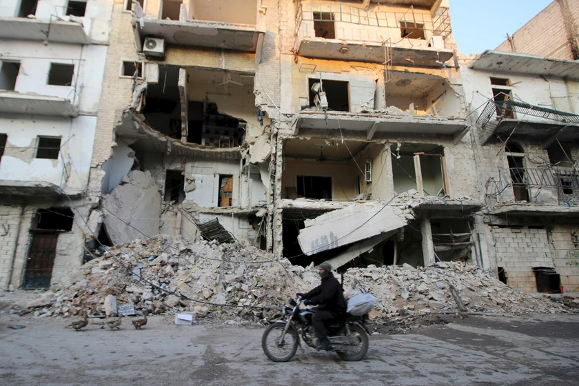 A man rides a motorcycle past damaged buildings in al-Myassar neighborhood of Aleppo, Syria January 31, 2016. Photo: Reuters/Abdalrhman Ismail