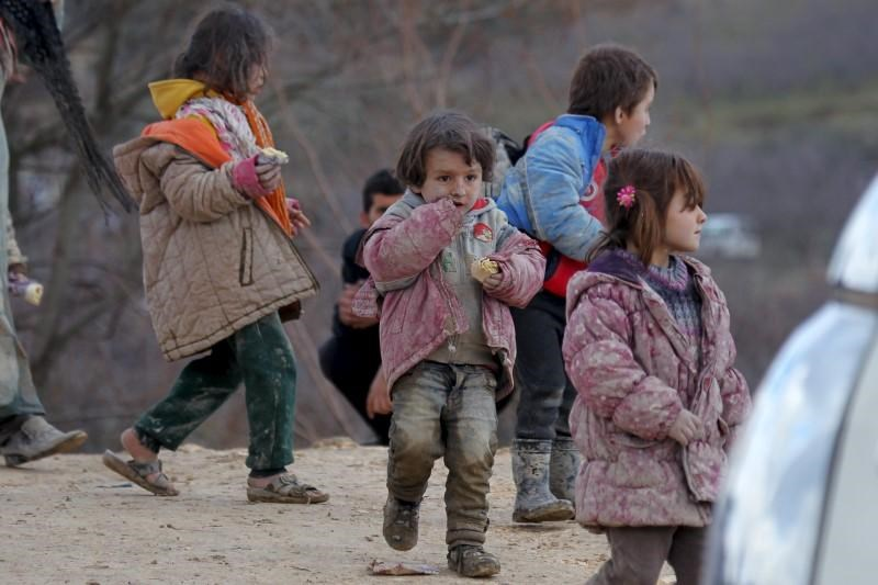Internally displaced children, covered with mud, wait with their families as they are stuck in the town of Khirbet Al-Joz, in Latakia countryside, waiting to get permission to cross into Turkey near the Syrian-Turkish border, Syria, February 7, 2016. Photo: Reuters/Ammar Abdullah