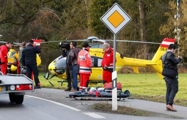 Rescuers and journalists stand in front of a rescue helicopter near Bad Aibling in southwestern Germany, February 9, 2016. Photo: Reuters/Michael Dalder