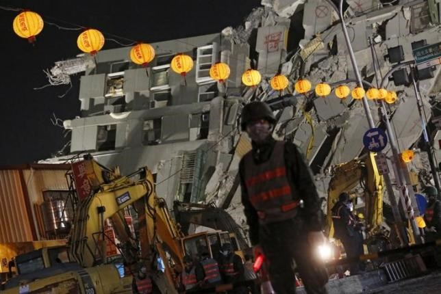 Soldiers stand guard in front of 17-story apartment building collapsed after an earthquake, on the first day of the Chinese Lunar New Year at Tainan, southern Taiwan February 8, 2016. Photo: Reuters/Tyrone Siu
