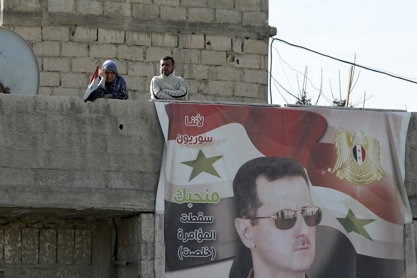 "Residents stand near a picture of Syria's president Bashar al-Assad in Wafideen Camp, which is controlled by Syrian government forces, in Damascus suburbs, Syria February 13, 2016. The text on the picture reads in Arabic: ""Because we are Syrian, we love you, down with the conspiracy, it's done."" Photo: Reuters/Omar Sanadiki"