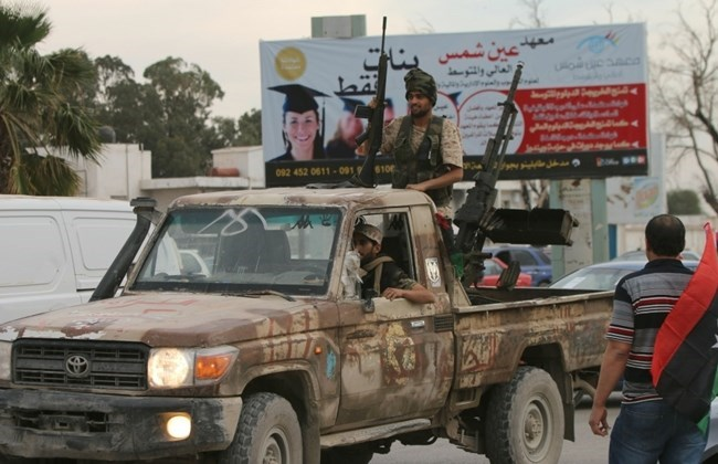 Armed Libyan men drive a vehicle during a demonstration marking the fifth anniversary of the Libyan revolution, in the city of Benghazi, on February 17, 2016. Photo: AFP/Abdullah Doma