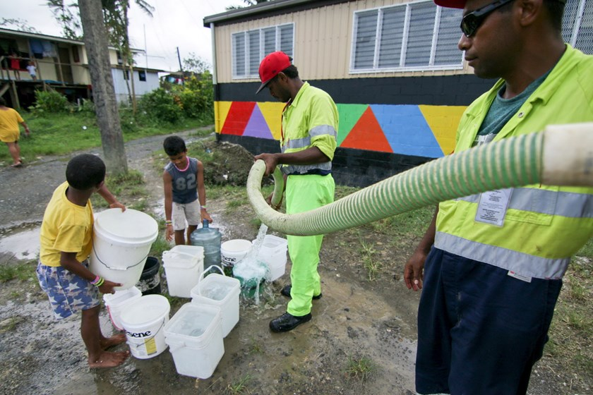 Workers from Suva's City Council fills residents' buckets with fresh water after power outages caused by Cyclone Winston stopped the pumps from working throughout Fiji's capital Suva, February 23, 2016. Photo: Reuters/Steven Saphore/Handout via Reuters
