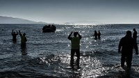 Members of the non-profit organization Emergency Response Center International (ERCI) gesture from the shore to a boat carrying refugees and migrants as it arrives in Mytilene on the northern Greek island of Lesbos, after crossing the Aegean sea from Turkey, on February 22, 2016. Photo: AFP/ARIS MESSINIS