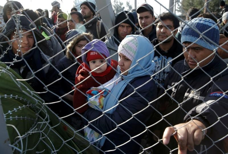 Migrants stand next to a border fence at the Greek-Macedonian border, after additional passage restrictions imposed by Macedonian authorities left hundreds of them stranded near the village of Idomeni, Greece, February 23, 2016. Photo: Reuters/Marko Djurica