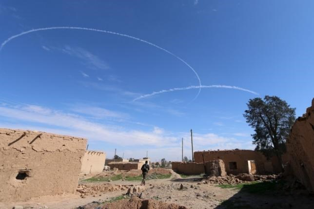 A Syria Democratic Forces fighter walks under contrails made by U.S. alliance air forces on the outskirts of al-Shadadi town, Hasaka countryside, Syria, February 19, 2016. Photo: Reuters/Rodi Said