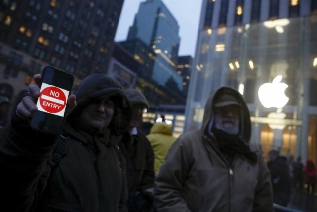 A demonstrator holds a sign during a protest against the FBI's request to extract data from iPhones in cases across the country, outside the Apple Store in New York February 23, 2016. Photo: Reuters/Shannon Stapleton