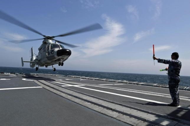 A Chinese navy sailor (R) guides a helicopter to land on Chinese destroyer Harbin during the Joint Sea-2014 naval drill outside Shanghai on the East China Sea, May 24, 2014. Photo: REUTERS/CHINA DAILY