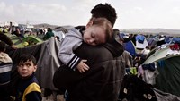 A baby sleeps in the arms of a man in the makeshift refugee and migrant camp at the Greek-Macedonian borders near the Greek village of Idomeni, on March 1, 2016, where thousands of people are stranded, as anger mounted over travel restrictions on migrants. Photo: AFP/Louisa Gouliamaki