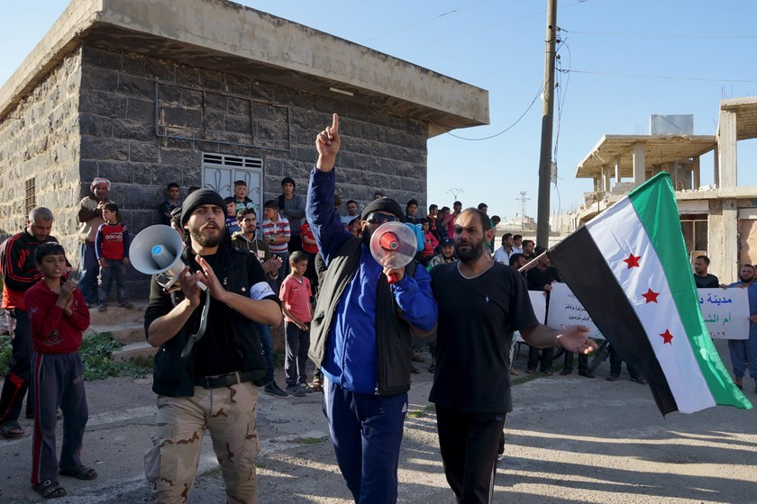 Activists shout slogans while carrying a Free Syrian Army flag during a protest against forces loyal to Syria's President Bashar al-Assad in the rebel-held town of Dael, in Deraa Governorate, Syria February 29, 2016. Photo: Reuters/Alaa Al-Faqir