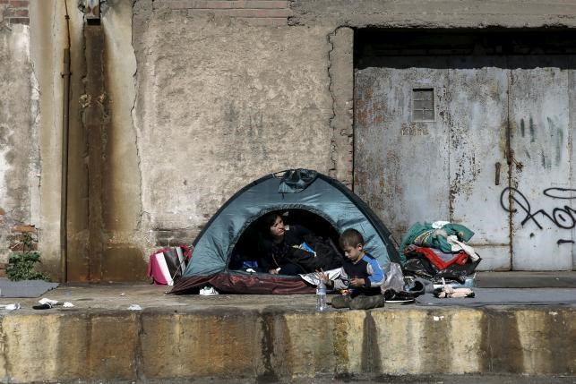A refugee is seen inside a tent as a child nearby, next to an old building at the port of Piraeus, near Athens, Greece, March 2, 2016. Photo: Reuters/Alkis Konstantinidis