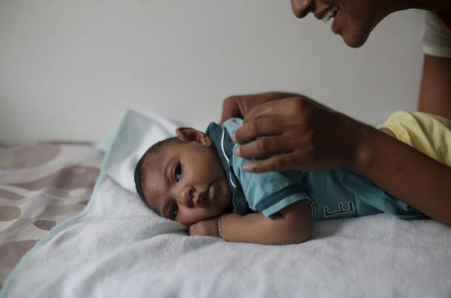 Mariam Araujo, 25, plays with Lucas, her 4-months old second child and born with microcephaly as they wait for a physiotherapy session in Pedro I hospital in Campina Grande, Brazil, February 17, 2016. Photo: Reuters/Ricardo Moraes