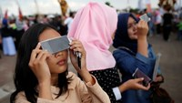 People test filters for watching a solar eclipse near the Ampera Bridge on the Musi River the day before thousands of people are expected to gather to witness the event in Palembang, South Sumatra province, Indonesia March 8, 2016. Photo: Reuters/Darren Whiteside