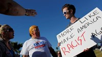 "Supporters (L) of Republican U.S. presidential candidate Donald Trump point and scream at an anti-Trump demonstrator (R) holding a sign reading ""More Like Make America Racist Again"" sign during a Trump campaign rally in Fountain Hills, Arizona March 19, 2016. Photo: Reuters/Ricardo Arduengo"