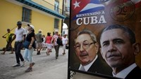 Tourists pass by images of U.S. President Barack Obama and Cuban President Raul Castro in a banner that reads ''Welcome to Cuba'' at the entrance of a restaurant in downtown Havana, March 17, 2016. Photo: Reuters/Alexandre Meneghini