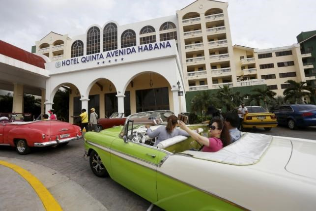 Tourists take a selfie while sitting in a vintage car outside the Quinta Avenida Habana Hotel in Havana, March 19, 2016. Photo: Reuters/Stringer