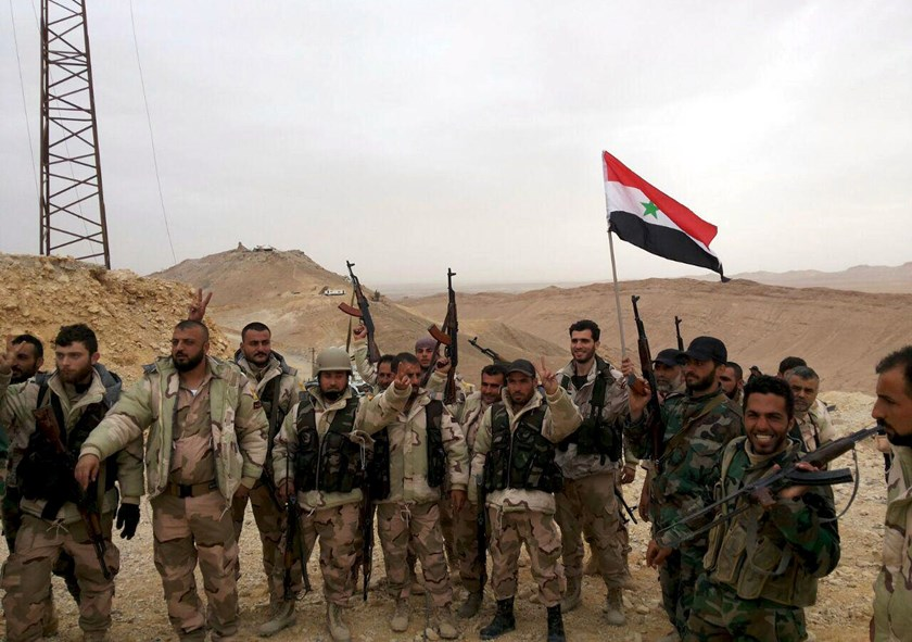 Forces loyal to Syria's President Bashar al-Assad flash victory signs and carry a Syrian national flag on the edge of the historic city of Palmyra in Homs Governorate, in this file handout picture provided by SANA on March 26, 2016. Photo: Reuters/SANA/Handout via Reuters/Files