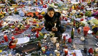A girl lights a candle as people pay tribute to the victims of Tuesday's bomb attacks at the Place de la Bourse in Brussels, Belgium, March 26, 2016. Photo: Reuters/Francois Lenoir