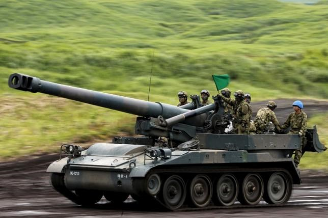 Japanese Ground Self-Defense Force soldiers ride on a 203mm self-propelled howitzer during an annual training session, which is based on a scenario to defend or retake islands in Japanese territory, near Mount Fuji at Higashifuji training field in Gotemba, west of Tokyo. Photo: Reuters/Yuya Shino