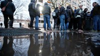 Migrants are reflected in a puddle as they queue in front of the compound of the Berlin Office of Health and Social Affairs (LAGESO) for their registration process, early morning in Berlin, Germany, February 2, 2016. Photo: Reuters/Fabrizio Bensch