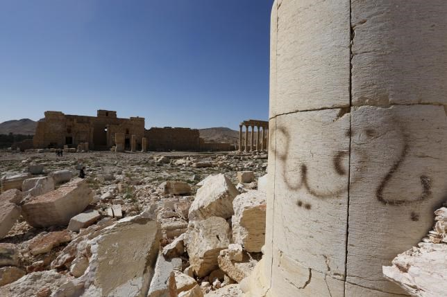 Graffiti (R) sprayed by Islamic State militants which reads ''We remain'' is seen at theTemple of Bel in historic city of Palmyra, in Homs Governorate, Syria April 1, 2016.Photo: REUTERS/OMAR SANADIKI