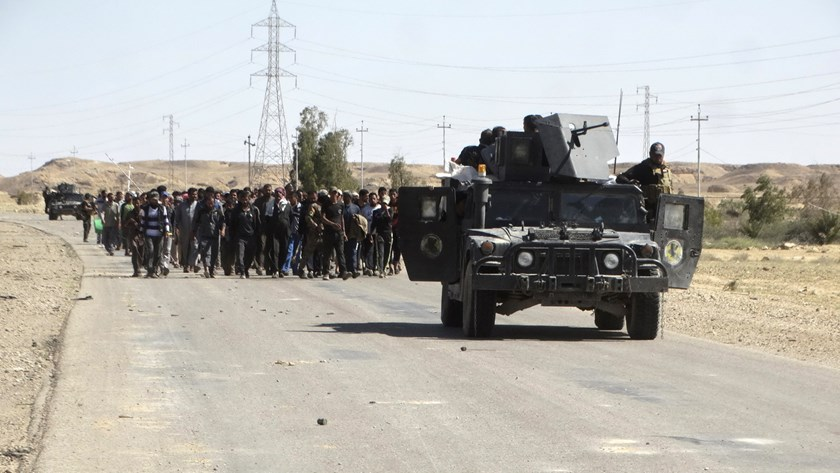 Iraqi security forces escort civilians who fled their homes due to the clashes between Iraqi security forces and Islamic state militants in the town of Hit in Anbar province, April 4, 2016. Photo: Reuters