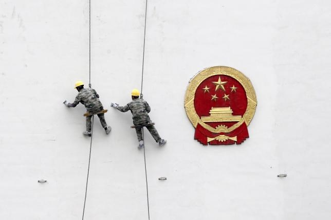 Workers paint a wall of a government building in Hangzhou, Zhejiang Province, China, in this March 26, 2016 file picture. Photo: Reuters/Chance Chan/Files