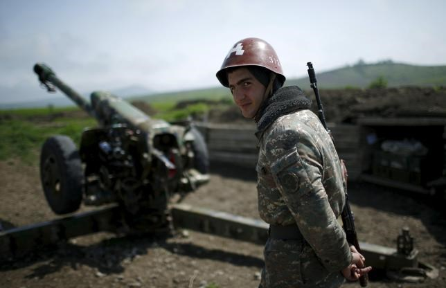 An ethnic Armenian soldier stands next to a cannon at the artillery positions near Nagorno-Karabakh's town of Martuni, April 8, 2016. Photo: Reuters