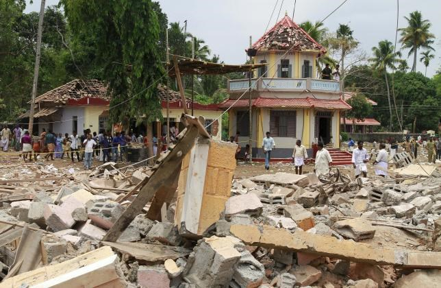 People stand next to debris after a broke out at a temple in Kollam in the southern state of Kerala, India, April 10, 2016. Photo: Reuters/Sivaram V