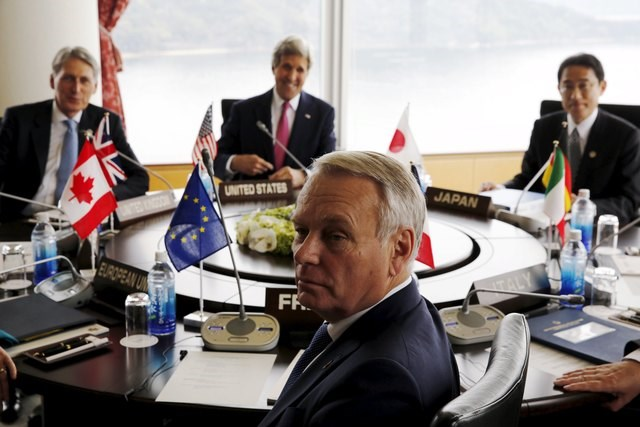 """France""""s Foreign Minister Jean-Marc Ayrault (foreground) sits with Britain""""s Foreign Minister Philip Hammond (back, L-R), U.S. Secretary of State John Kerry and Japan""""s Foreign Minister Fumio Kishida for the start of the first working session of the G7 foreign minister meetings in Hiroshima, Japan April 10, 2016. Photo: Reuters/Jonathan Ernst"""